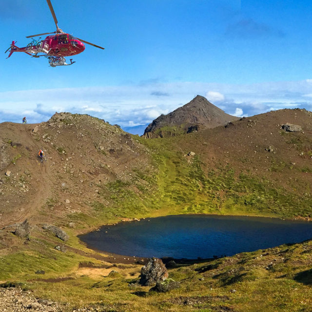 Bikerack on helicopter flying away from mountaintop